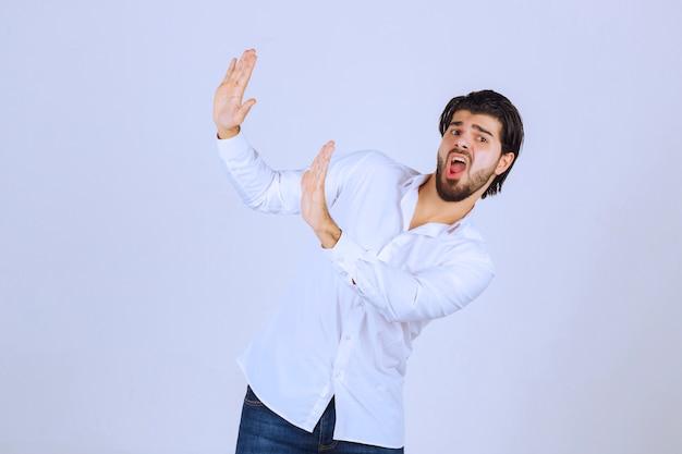 Uomo in camicia bianca che cerca di fermare qualcosa.