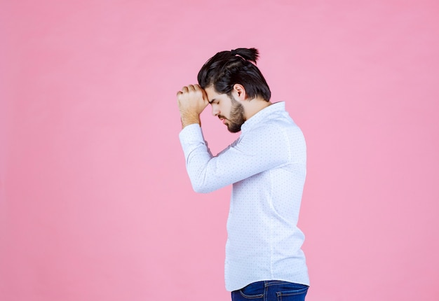 Man in a white shirt uniting hands and praying.