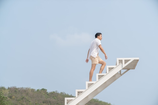 Man in white shirt walking up on the staircase.