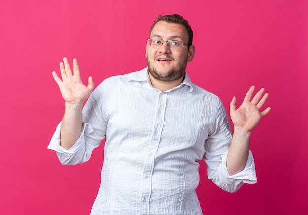 Man in white shirt wearing glasses  happy and positive raising arms standing over pink wall