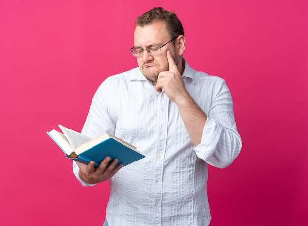 Man in white shirt wearing glasses holding book looking at it with pensive expression thinking standing on pink