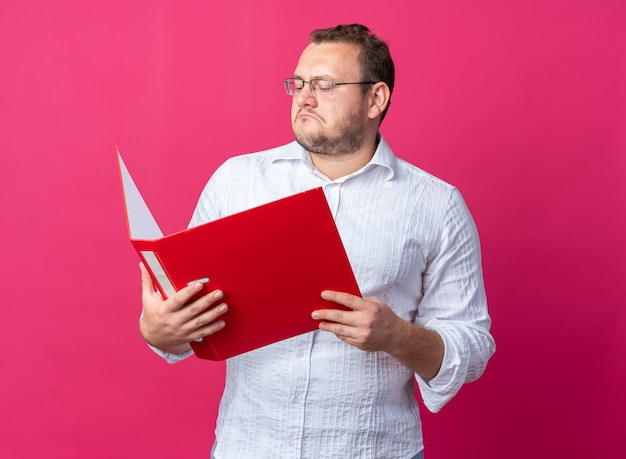 Man in white shirt wearing glasses holding office flder looking at it with serious face standing on pink