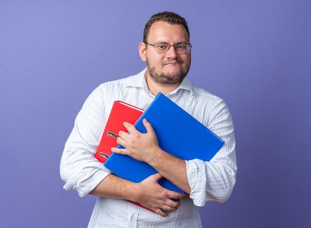 Uomo in camicia bianca con gli occhiali che tengono le cartelle dell'ufficio facendo la bocca storta con l'espressione delusa in piedi sul muro blu