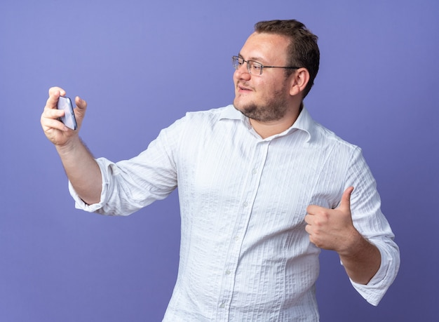 Man in white shirt wearing glasses holding smartphone having video call happy and positive showing thumbs up standing over blue wall