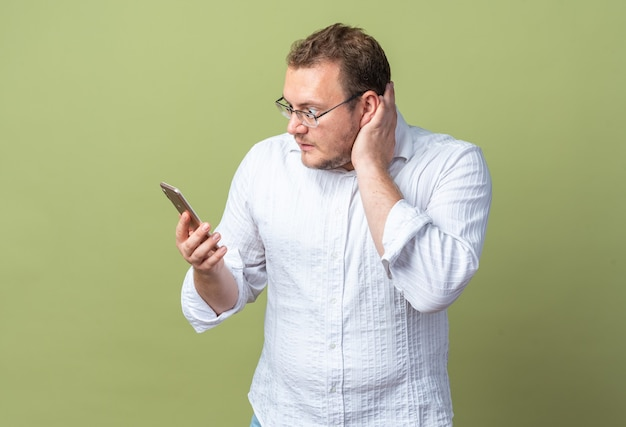 Uomo in camicia bianca con gli occhiali che tiene in mano uno smartphone che lo guarda confuso e molto ansioso in piedi sul verde