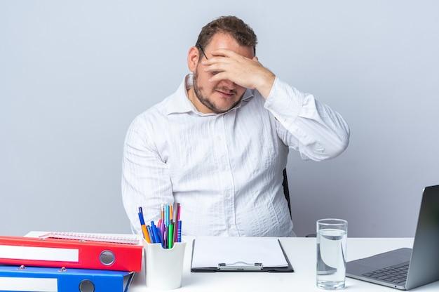 Uomo in camicia bianca con gli occhiali che sembra infastidito e stanco cono gli occhi con la mano seduto al tavolo con le cartelle dell'ufficio del computer portatile e appunti su bianco