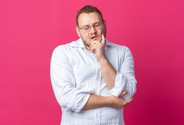 Man in white shirt wearing glasses looking down puzzled standing on pink