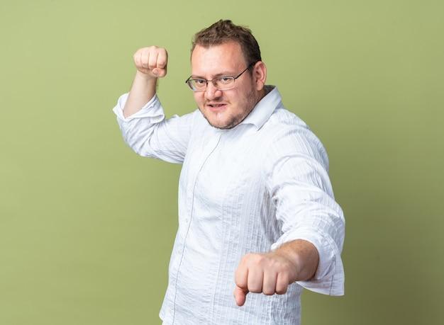 Uomo in camicia bianca con gli occhiali che guarda davanti con la faccia seria che stringe i pugni in piedi sul muro verde