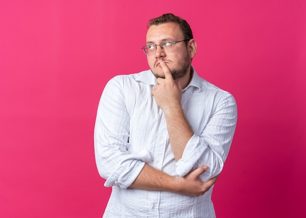 Man in white shirt wearing glasses looking up puzzled standing on pink