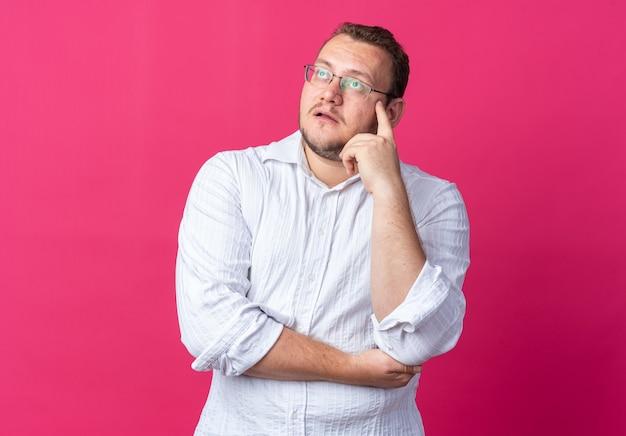 Uomo in camicia bianca con gli occhiali che guarda perplesso in piedi sul rosa