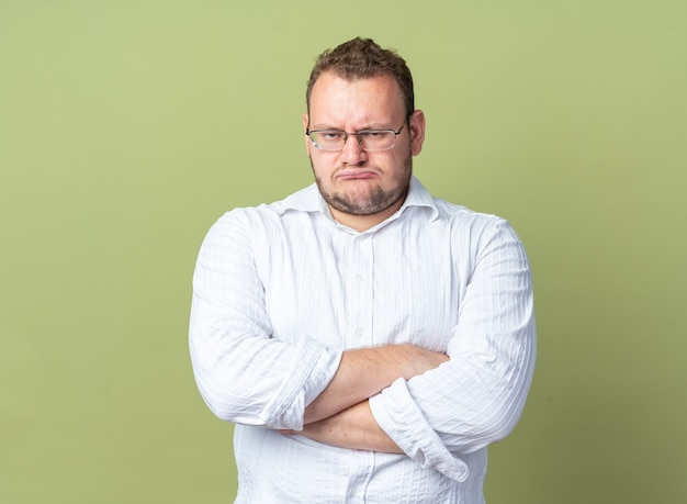 Uomo in camicia bianca con gli occhiali che guarda con la faccia accigliata con le braccia incrociate