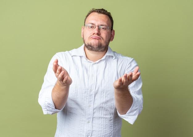 Uomo in camicia bianca con gli occhiali che fa la bocca storta con un'espressione delusa che alza le braccia in piedi sul muro verde