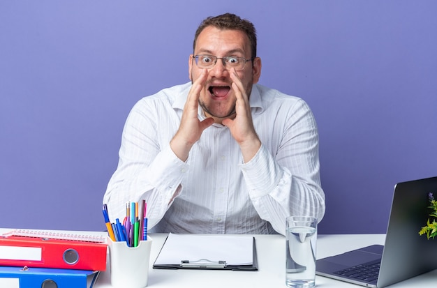 Man in white shirt wearing glasses shouting with hands over head being happy and excited shouting sitting at the table with laptop and office folders over blue background working in office