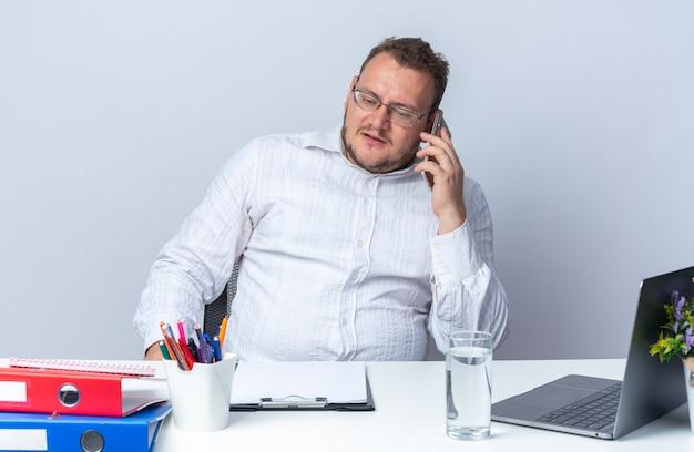 Uomo in camicia bianca con gli occhiali che parla al telefono cellulare con una faccia seria seduto al tavolo con cartelle per ufficio portatile e appunti su bianco
