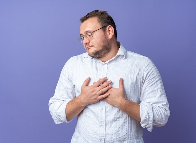 Man in white shirt wearing glasses with hands on his chest happy and positive feeling thankful standing over blue wall