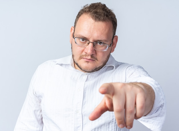 Man in white shirt wearing glasses with serious face pointing with index finger at you standing on white