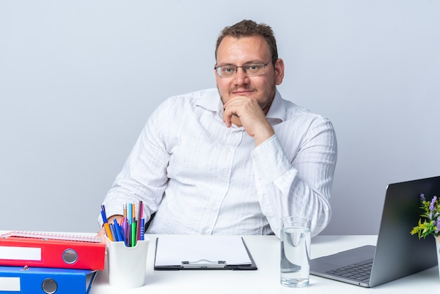 Man in white shirt wearing glasses  with smile on smart face sitting at the table with laptop office folders and clipboard over white wall working in office