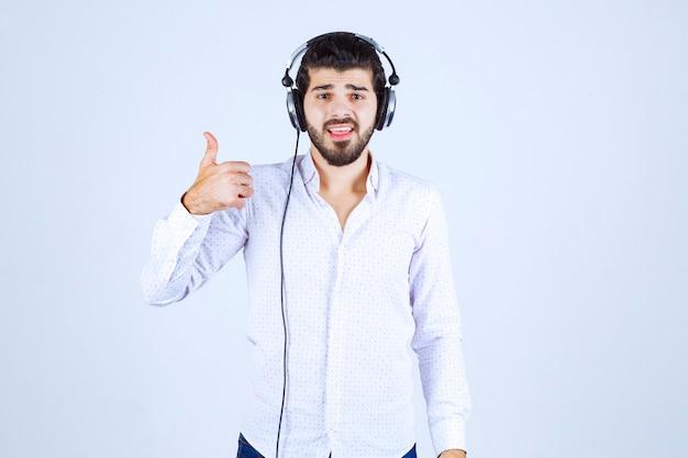 Uomo in camicia bianca che indossa le cuffie e si gode la musica