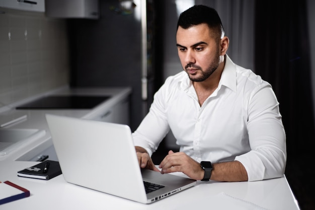 Man in white shirt websurfing with laptop in home kitchen