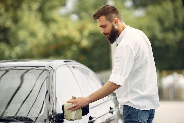 Man in a white shirt wipes a car in a car wash