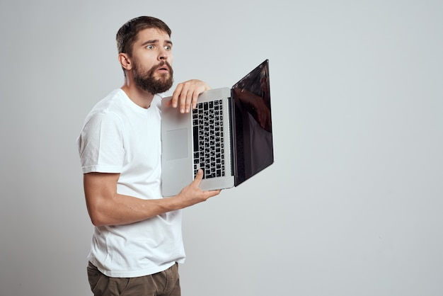 A man in a white shirt with a laptop in his hands