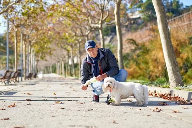 男白い小さな犬の散歩公園