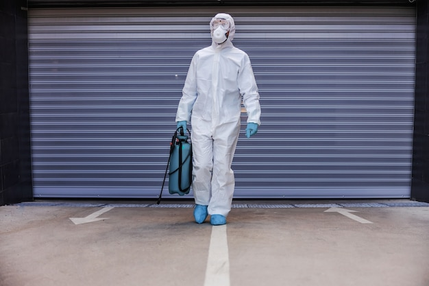 Man in white sterile uniform with rubber gloves holding sprayer with disinfectant and walking towards camera in garage.