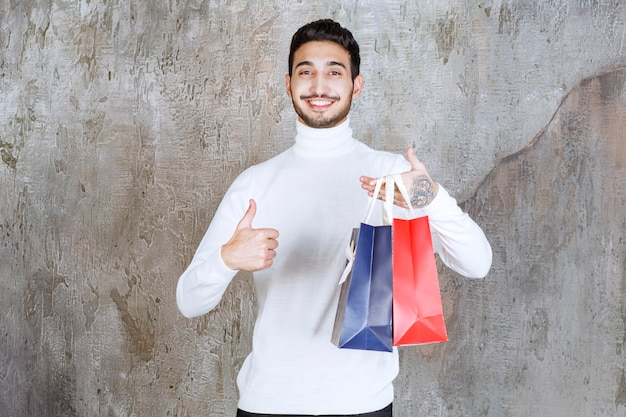 Man in white sweater holding red and blue shopping bags and showing thumb up.