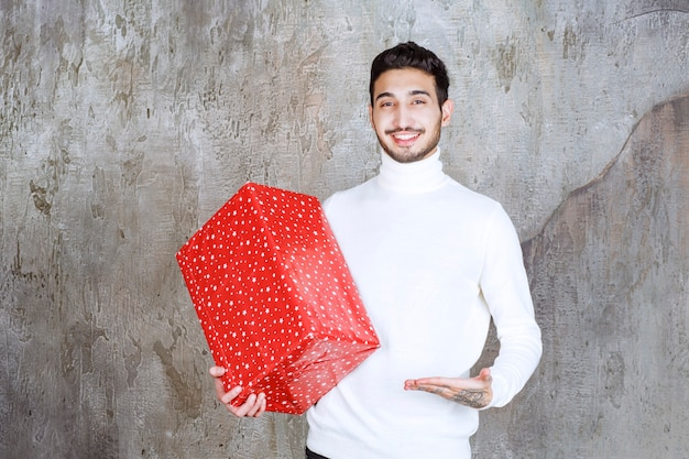 Man in white sweater holding a red gift box with white dots on it.