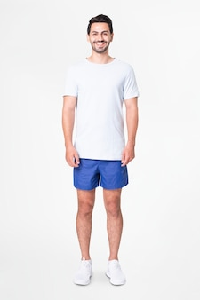 Man in white t-shirt and blue shorts with design space full body