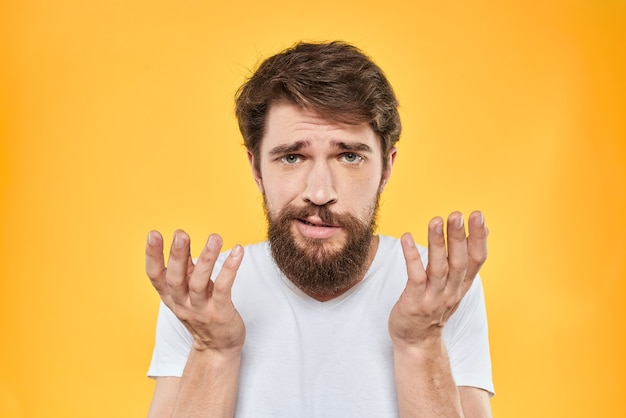 Man in white t-shirt gesturing with hands and displeased on yellow