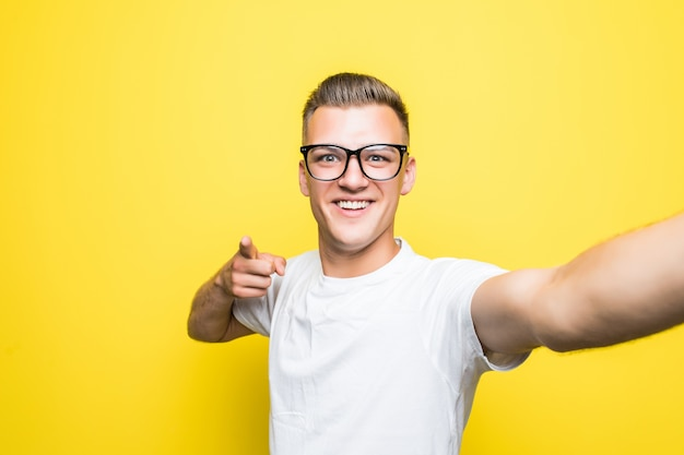 Man in white t-shirt and glasses makes something on his phone and takes selfie pictures holding phone