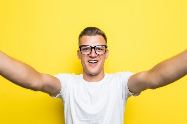L'uomo in maglietta bianca e occhiali fa qualcosa sul suo telefono e scatta foto selfie tenendo il telefono