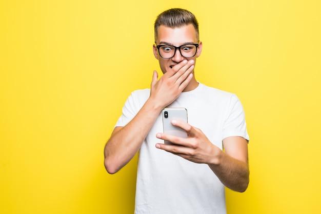 L'uomo in maglietta bianca e occhiali fa qualcosa sul suo telefono e scatta foto selfie isolate su giallo