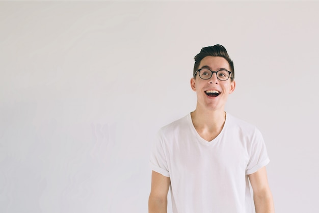 Man in white t-shirt and glasses with big smile isolated on white . a very kind student has a good mood