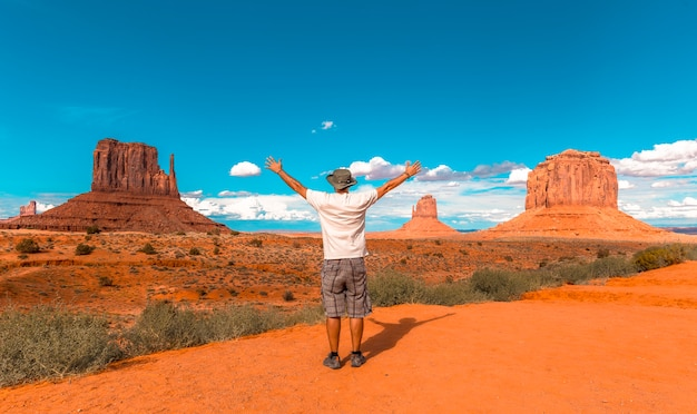 Man in white t-shirt and green hat with arms raised in monument valley national park at the mittens