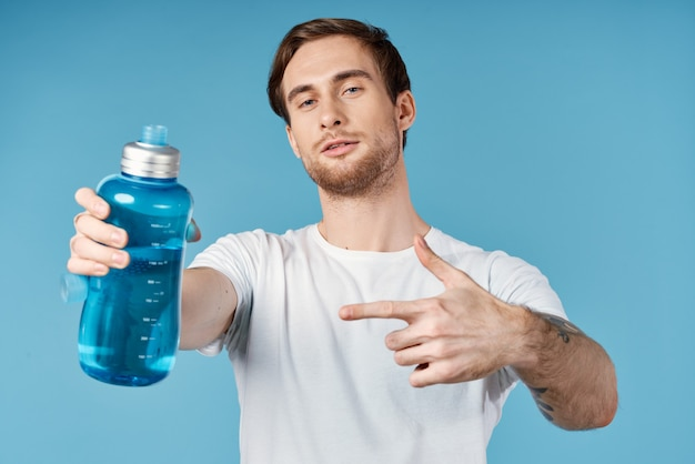 Man in white t-shirt holding a bottle of water