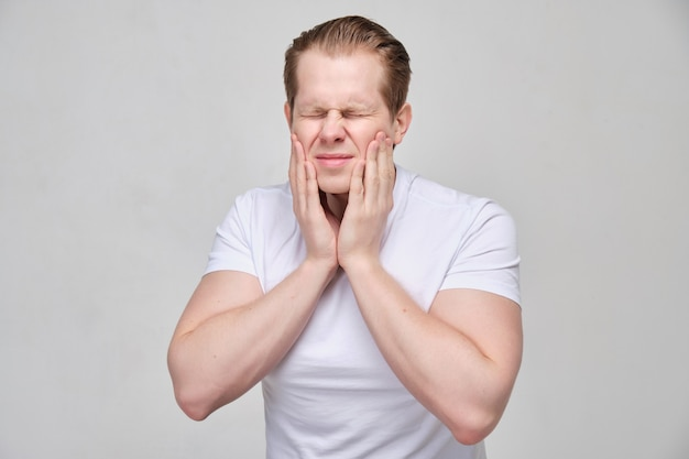 A man in a white t-shirt holds on to his jaw. the concept of toothache.
