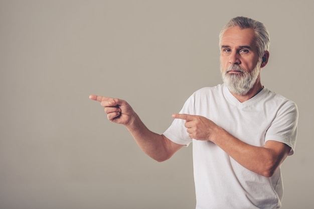 Man in white t-shirt is pointing to the side.