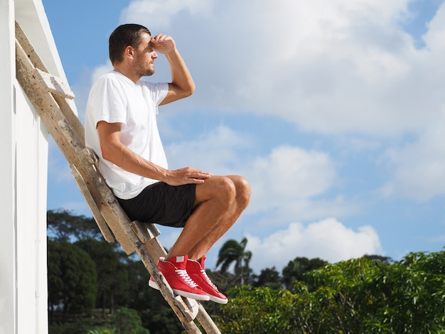 A man in a white t-shirt and red sneakers sits on a wooden staircase looking far.