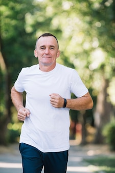 Man in white t-shirt running in a park