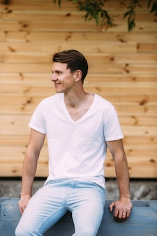 Man in white t-shirt sitting and smiling