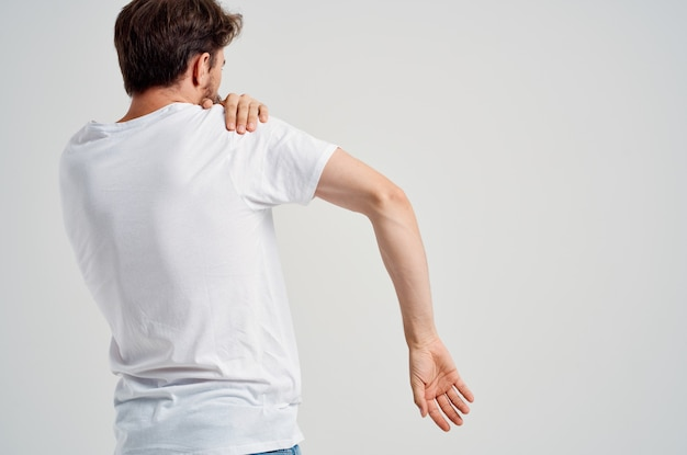 Man in a white t-shirt stress medicine pain in the neck light background. high quality photo