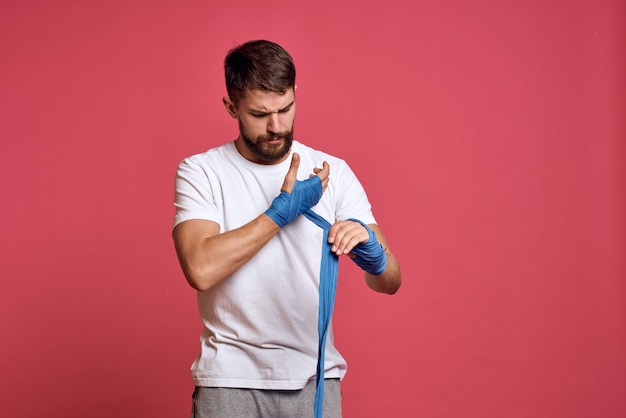 Man in white t-shirt ties his hand with a bandage martial arts pink space