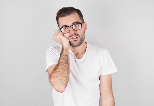 Man in a white t-shirt with a beautiful beard looks tired to the side.