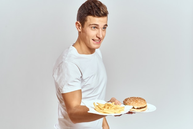 A man in a white t-shirt with fast food burger in his hands