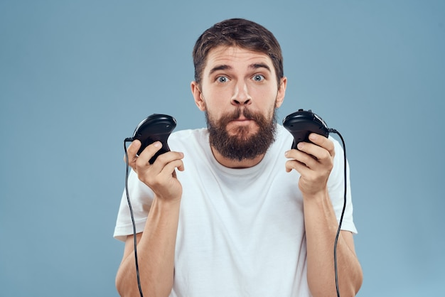 A man in a white t-shirt with a joystick in his hands game console entertainment emotions