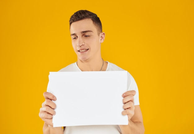 A man in a white t-shirt with a sheet of paper on a yellow background copy space mockup