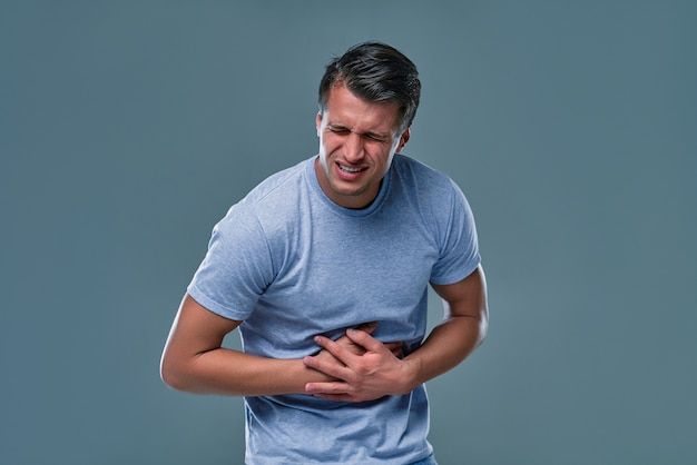 Man in white t-shirt with stomachache on gray room