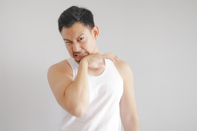 Man in white tank top with hot weather expression. concept of hot weather of the sun in asia.